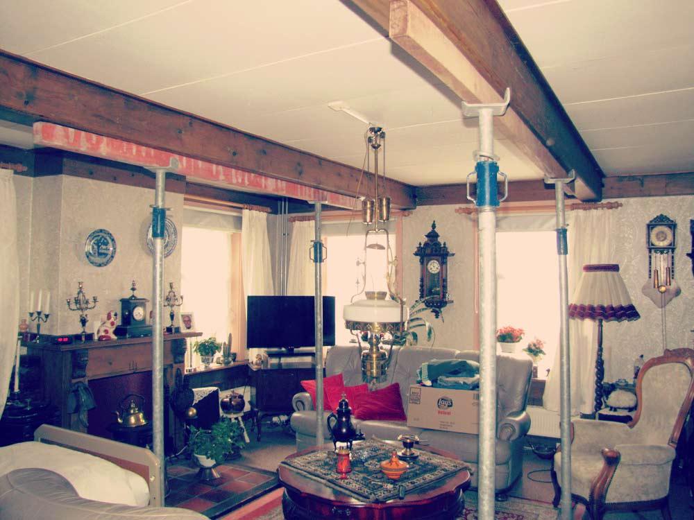 een woonkamer met een aantal metalen stutten tussen het meubilair